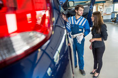 Mechaniker Discussing With Businesswoman mit dem Auto an der Garage Stockfoto