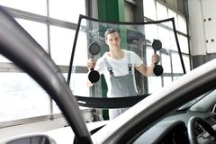 Mechaniker in einer Garage ersetzt defekte Windschutzscheibe eines Autos Stockfotos