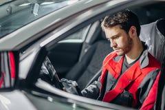 Mechaniker Examining Car Engine mithilfe des Laptops Stockfotografie