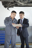 Mechaniker Explaining zum Geschäftsmann, ihm den Bill zeigend Stockfoto