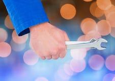 Mechaniker Hand, das Schlüssel mit funkelndem hellem bokeh Hintergrund hält Stockfotos