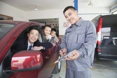 Mechaniker Helping Family mit ihrem Auto lizenzfreies stockbild