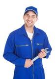 Mechaniker im blauen Overall, der Schlüssel hält Stockfotos