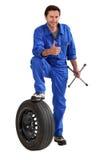 Mechaniker mit dem Reifen und Schlüssel, einen Daumen aufgebend Lizenzfreie Stockfotografie