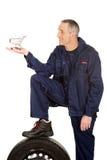 Mechaniker mit einem Reifen und einem Korb Lizenzfreie Stockfotos