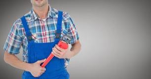 Mechaniker mit rotem Schlüssel gegen grauen Hintergrund Stockbild