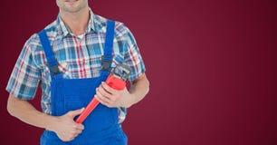 Mechaniker mit rotem Schlüssel gegen kastanienbraunen Hintergrund Lizenzfreies Stockfoto