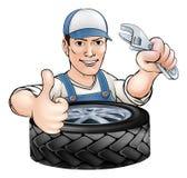 Mechaniker mit Schlüssel und Reifen Stockfoto