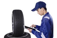 Mechaniker mit Untersuchungsreifen der Tablette Lizenzfreies Stockfoto