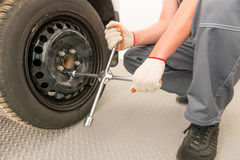 Mechaniker schraubt das Rad ein Schlüssel ab Lizenzfreies Stockfoto
