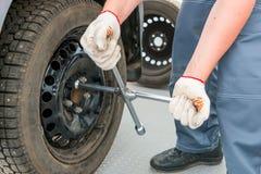 Mechaniker schraubt Nüsse auf dem Rad ein Schlüssel ab Stockfotografie