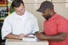 Mechaniker-Showing Customer An-Rechnung stockfotografie