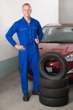 Mechaniker Standing Besides Stack von Reifen Lizenzfreie Stockfotos