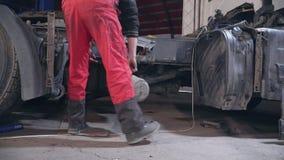 Mechaniker und Arbeitskräfte reparieren einen LKW an der Station stock footage