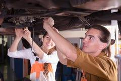 Mechaniker und Assistent, die an der Werkstatt arbeiten Lizenzfreie Stockfotografie