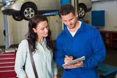 Mechaniker und Kunde, die zusammen sprechen Lizenzfreie Stockbilder