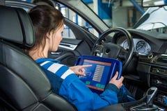 Mechaniker Using Tablet Computer im Auto an der Garage Stockfoto