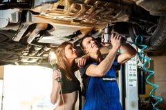 Mechaniker zieht die Bolzen der Unterseite des Autos fest Stockbilder