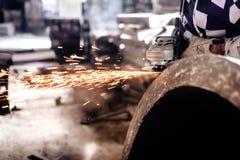 Mechanikerarbeitskraft, die Schleifer für das Polieren eines Eisenblockes verwendet Stockfotografie