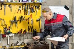 Mechanikerarbeitskraft, die seine Anweisungen studiert Lizenzfreie Stockbilder