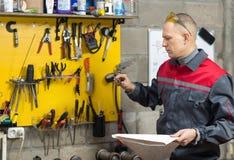 Mechanikerarbeitskraft, die seine Anweisungen studiert Stockbilder