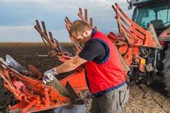 Mechanikerfestlegungspflug auf dem Traktor stockfotografie