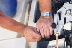 Mechanikerhände, die Bootsmotor reparieren lizenzfreies stockfoto