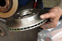 Mechanikerhand, die neue Scheibenbremse befestigt. Lizenzfreies Stockfoto