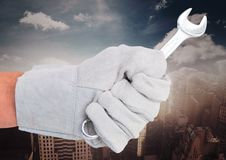 Mechanikerhand mit Schlüssel gegen undeutliche Skyline Stockfoto