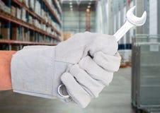 Mechanikerhand mit Schlüssel gegen undeutliches Lager Stockfotos