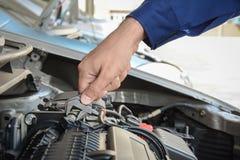 Mechanikerhand mit Schlüsselfestlegungsautomotor Stockfotos