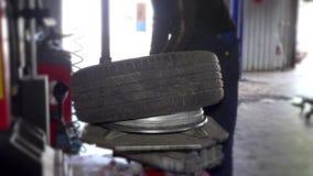 Mechanikerkerl im Abnutzungsmontagereifen der schmutzigen Arbeit auf Radfelge stock video