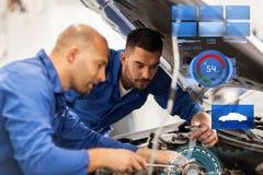 Mechanikermänner mit dem Schlüssel, der Auto an der Werkstatt repariert Lizenzfreie Stockbilder