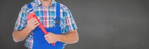 Mechanikermann, der einen Schlüssel gegen grauen Hintergrund hält Lizenzfreie Stockfotografie