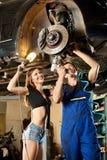 Mechanikermann und sexy Frau, die Auto auf Hebebühne reparieren Lizenzfreie Stockfotos