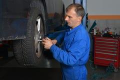Automechaniker, der Radnüsse festzieht lizenzfreies stockfoto