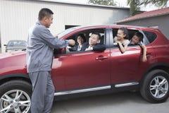 Mechanisch Giving Car Keys aan Familie stock foto's