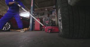 Mechanisch herstelleropkrikken omhoog een auto voor verandering een band stock videobeelden