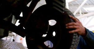 Mechanisch het bevestigen autowiel in garage 4k stock video