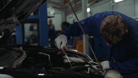 Mechanisch het controleren olieniveau in de van het de mensenportret van de autoworkshop van de de motorauto de reparatiedienst stock video