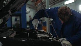 Mechanisch het controleren olieniveau in de van het de mensenportret van de autoworkshop van de de motorauto de reparatiedienst stock footage