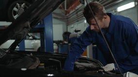 Mechanisch het controleren olieniveau in de van het de mensenportret van de autoworkshop van de de motorauto de reparatiedienst stock videobeelden