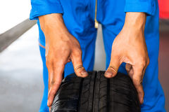 Mechanisch het houden en het controleren autowiel in de dienst van de autogarage Royalty-vrije Stock Foto's