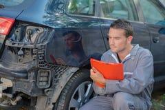 Mechanisch holdingsklembord die schade aan achterauto bekijken stock fotografie