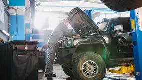Mechanisch mannetje die in automobiele garage kap van de auto controleren luxe SUV, brede hoek Stock Foto's
