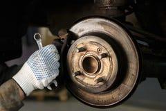Mechanisch in seiner Werkstatt, die Bremsscheiben ersetzte stockfotografie