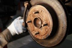 Mechanisch in seiner Werkstatt, die Bremsscheiben ersetzte stockfotos