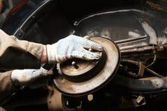 Mechanisch in seiner Werkstatt, die Bremsscheiben ersetzte lizenzfreies stockbild