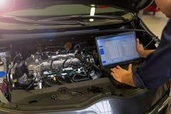 Mechanisch Using Laptop While die Motor van een auto onderzoeken Royalty-vrije Stock Fotografie
