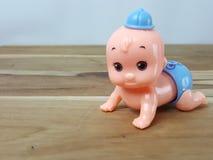 Mechanisch wickeln Sie oben kriechendes Babyspielzeug auf hölzernem Hintergrund lizenzfreie stockfotos